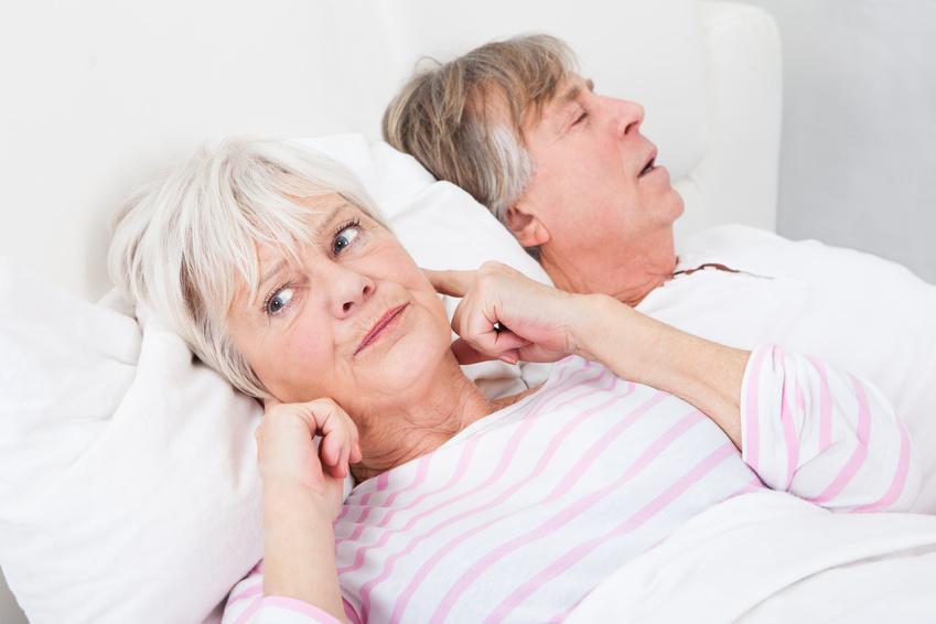 Femme qui dort à côté de son mari qui ronfle